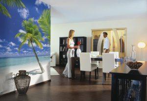 Ambiente decorado com painel fotográfico de praia com coqueiros